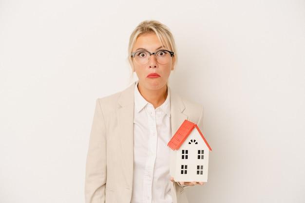 白い背景で隔離の家のモデルを保持している若い不動産業者の女性は肩をすくめると混乱した目を開いています。