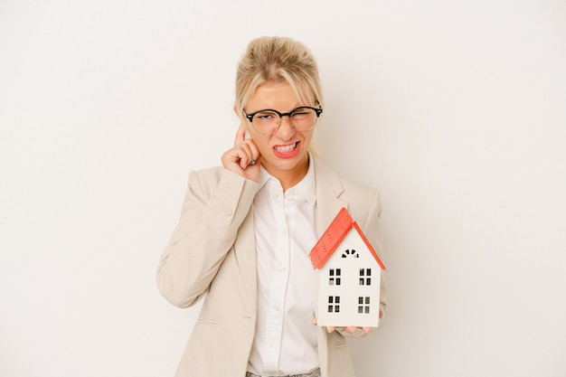 Young real estate agent woman holding a home model isolated on white background covering ears with hands.