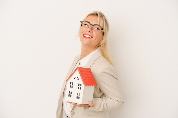 Young real estate agent woman holding a home model isolated on white background looks aside smiling, cheerful and pleasant.