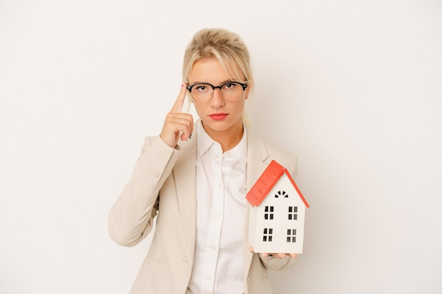 Young real estate agent woman holding a home model isolated on white background pointing temple with finger, thinking, focused on a task.