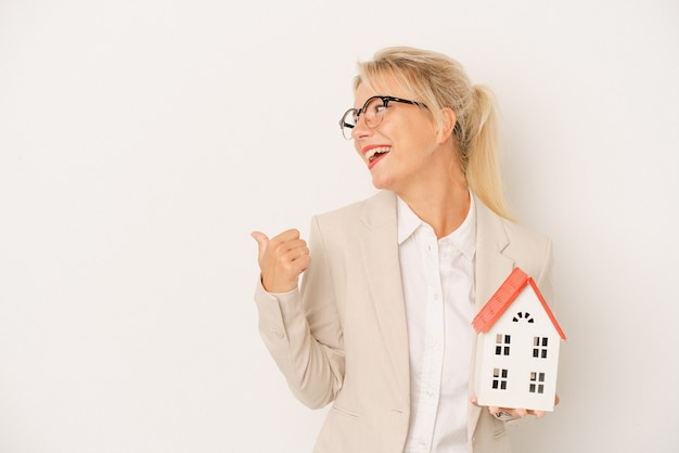 Young real estate agent woman holding a home model isolated on white background points with thumb finger away, laughing and carefree.