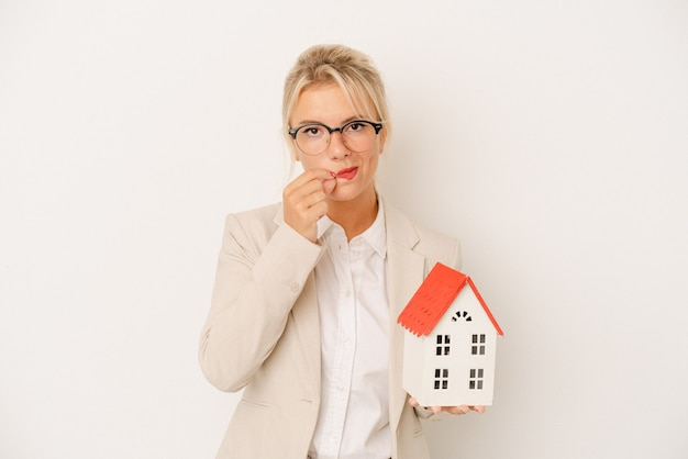 Young real estate agent woman holding a home model isolated on white background with fingers on lips keeping a secret.