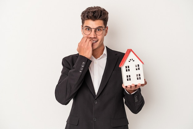 Young real estate caucasian agent isolated on white background biting fingernails, nervous and very anxious.