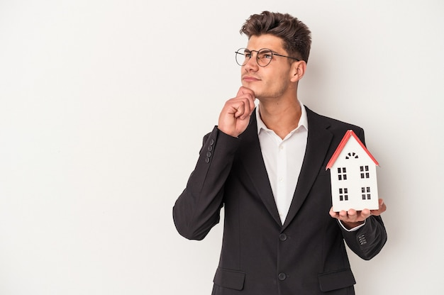 Young real estate caucasian agent isolated on white background looking sideways with doubtful and skeptical expression.