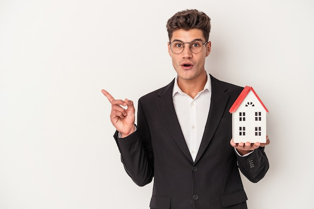 Young real estate caucasian agent isolated on white background pointing to the side