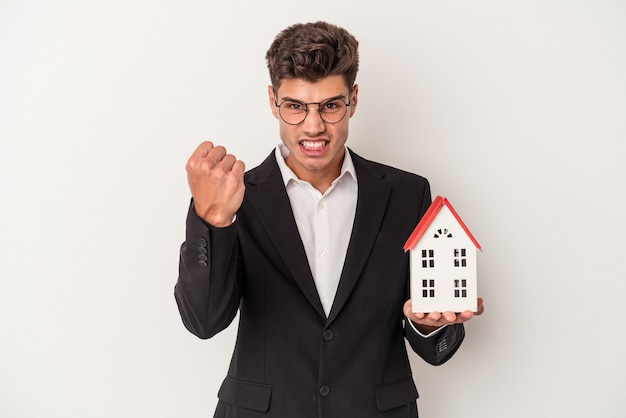 Young real estate caucasian agent isolated on white background showing fist to camera, aggressive facial expression.