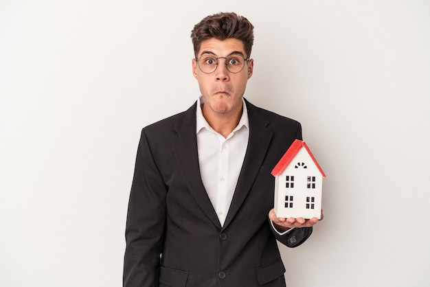 Young real estate caucasian agent isolated on white background shrugs shoulders and open eyes confused.