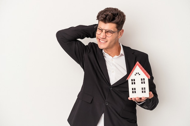 Young real estate caucasian agent isolated on white background touching back of head, thinking and making a choice.