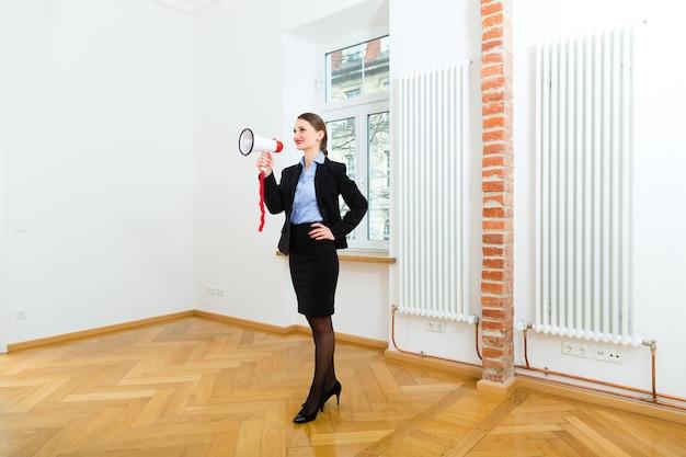 젊은 부동산 중개인이 아파트에 있고 그녀는 확성기로 광고를합니다.