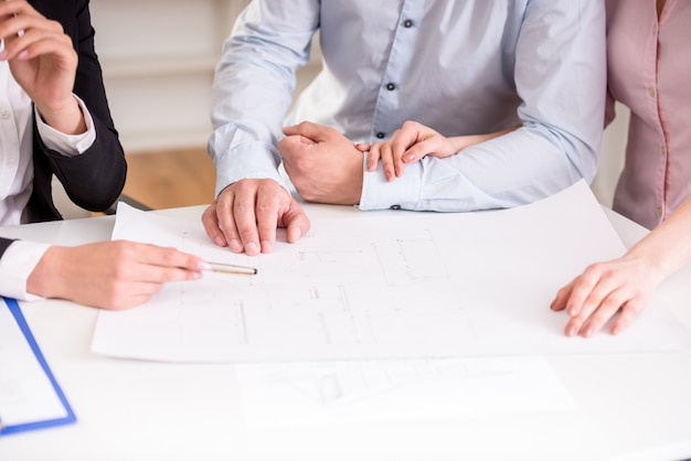Young realtor showing contract with apartment to couple.