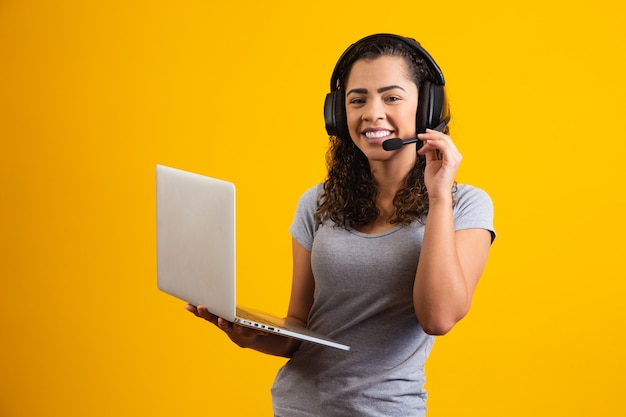 Young receptionist woman working with notebook and headset.