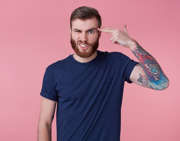 Young red-bearded frowning guy, can't find a way out, displeased and angry, shows headshots, scowl and grin isolated over pink background.
