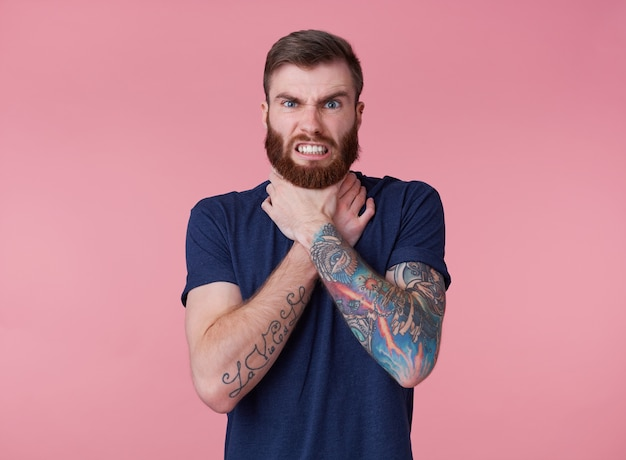 Young red-bearded frowning guy, can't find a way out, displeased and angry, trying to strangle himself, scowl and grin isolated over pink background.