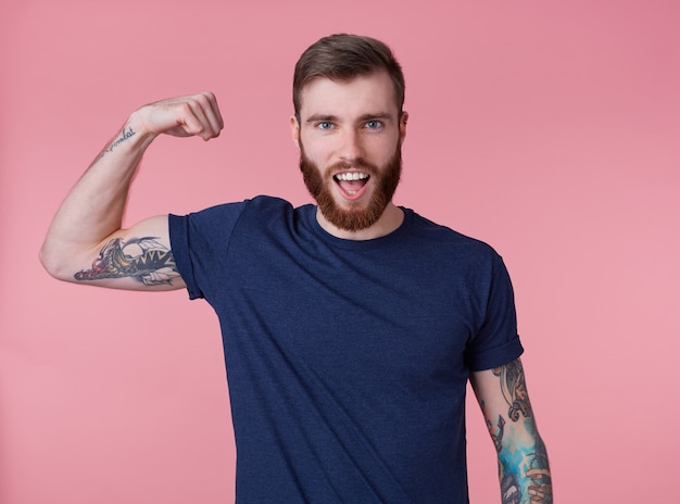 Young red-bearded handsome manful guy demonstrates biceps and strength with wide open mouth, looking at the camera isolated over pink background.