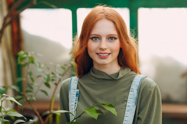 Молодой красный портрет женщины фермера волос смотря и улыбка в парнике. весенняя концепция домашнего садоводства.