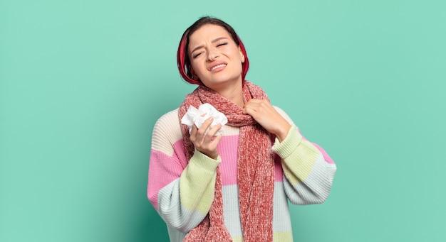 Молодая женщина с рыжими волосами чувствует стресс, тревогу, усталость и разочарование, тянет за шею рубашки, выглядит разочарованной концепцией проблемного гриппа