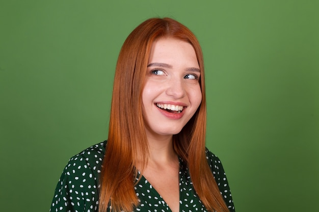 Young red hair woman on green wall smile  and laugh, in good mood, positive emotions