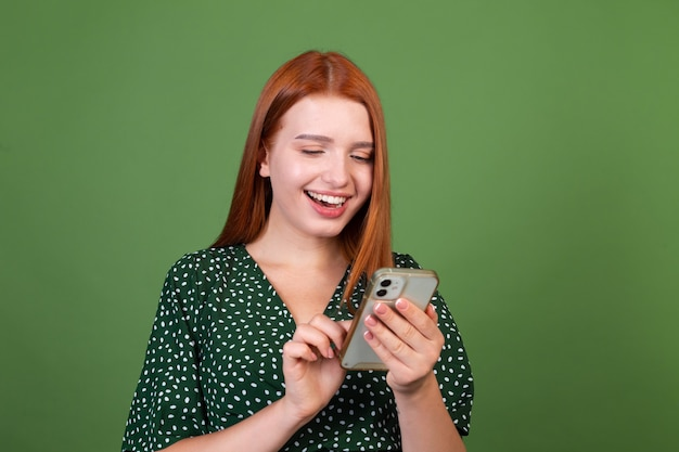 Young red hair woman on green wall with  mobile phone happy positive excited