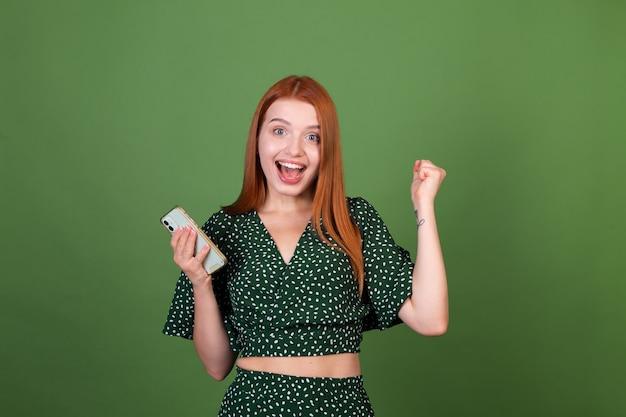 La giovane donna dei capelli rossi sulla parete verde con il telefono cellulare che manda un sms che chatta eccitato mostra il gesto del vincitore