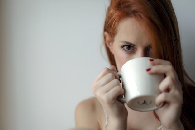 自宅で温かい飲み物を持つ若い赤髪の女性