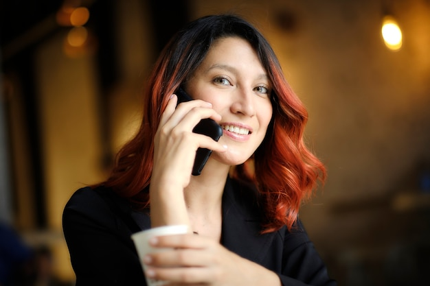 Молодая женщина с рыжими волосами держит чашку во время звонка
