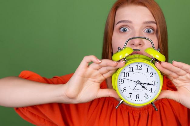 目覚まし時計を保持している緑の壁にカジュアルなオレンジ色のブラウスを着た若い赤い髪の女性眠い疲れた疲れた