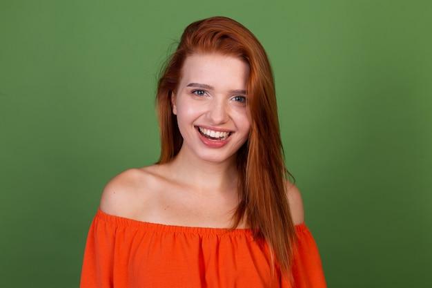 Молодая рыжая женщина в повседневной оранжевой блузке на зеленой стене смотрит в камеру, взволнованная улыбка, смех