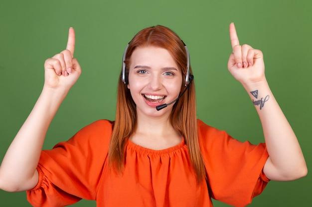 녹색 벽 관리자 콜 센터 헬프 라인 작업자가 손가락을 위로 가리키며 웃는 오렌지색 블라우스를 입은 젊은 빨간 머리 여성