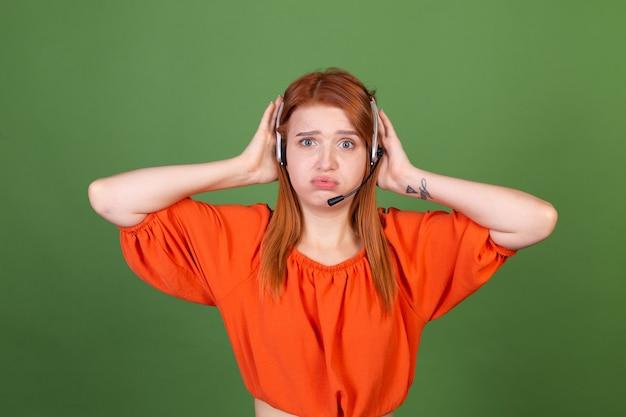 녹색 벽 관리자 콜 센터 헬프 라인 직원이 헤드폰을 끼고 지친 이야기를 하는 캐주얼 오렌지 블라우스를 입은 젊은 빨간 머리 여성