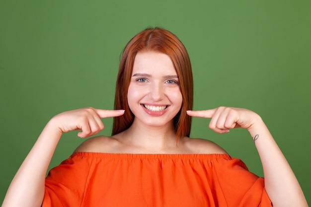 Молодая рыжая женщина в повседневной оранжевой блузке на зеленой стене указывает пальцами на белые зубы, идеальная улыбка