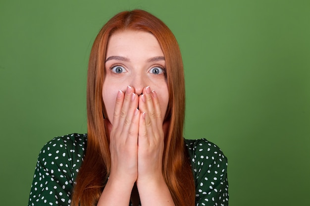 Молодая женщина с рыжими волосами на зеленой стене шокирована, удивлена, удивлена