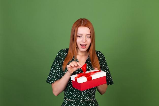 Молодая женщина с красными волосами на зеленой стене с подарочной коробкой, счастливая, взволнованная, пораженная, удивленная
