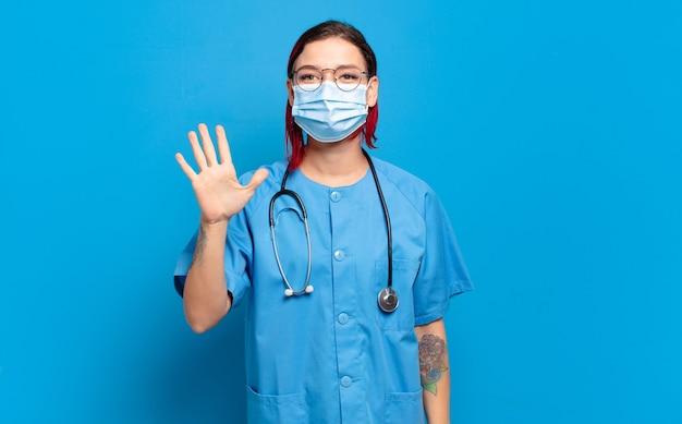 若い赤い髪の女性は笑顔でフレンドリーに見え、前に手を出して5番または5番を示し、カウントダウンします。病院の看護師の概念