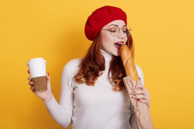 若い赤い髪の女性が長いパンを噛んで、黄色のコーヒーをテイクアウトします。