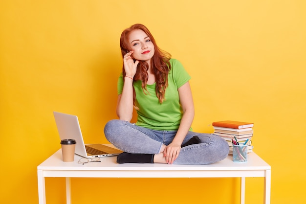 Young red haired female wearing green t shirt and jeans, satisfied student being tired from learning for long time