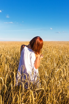 A young red-haired girl enjoys the beauty of a wheat field and a beautiful blue sky