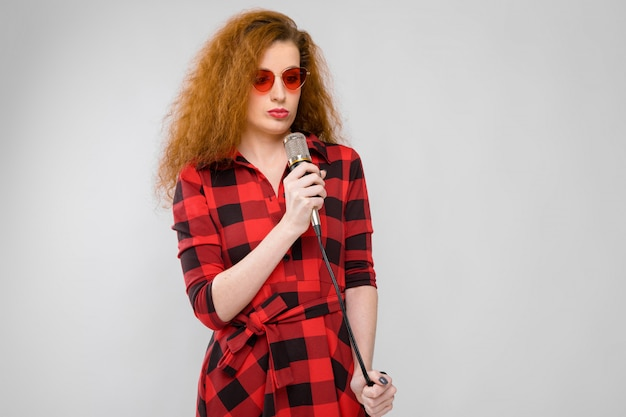 Молодая рыжеволосая девушка в красной клетчатой рубашке. молодая девушка в красных очках. молодая девушка стоит с микрофоном