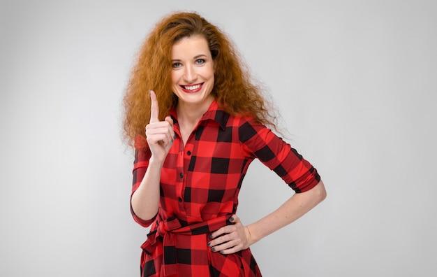 Молодая рыжеволосая девушка в красной клетчатой рубашке. молодая девушка показывает указательный палец