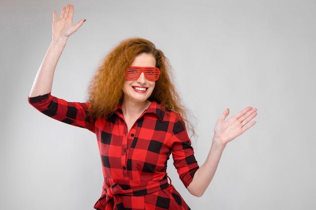 Молодая рыжая девушка в красной клетчатой рубашке.