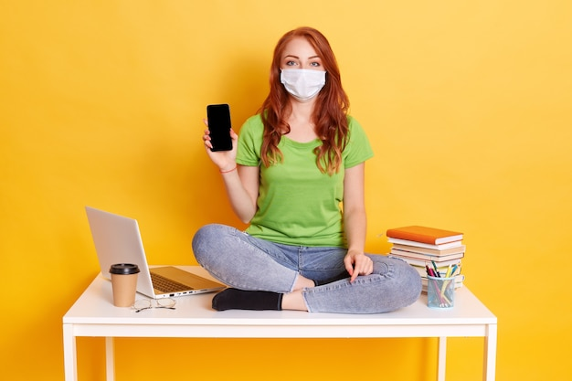 Молодая рыжеволосая девушка в респираторной маске держит смартфон с пустым экраном, рекомендует новое устройство, дистанционное обучение, карантин, сидит на столе с книгами, ноутбуком, ручками.