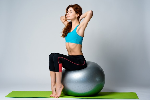 Young red haired girl is sitting on gym ball.