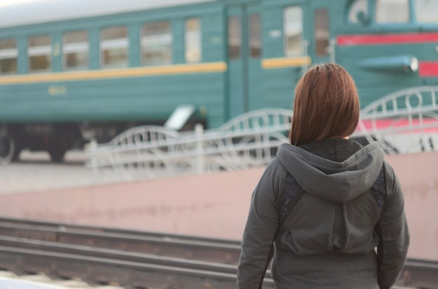 A young red-haired girl is standing on the railway platform and watching the departing train.