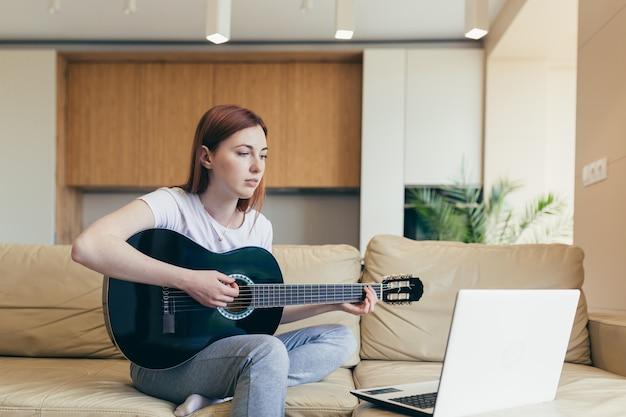 若い赤い髪の少女は、ビデオチュートリアルのレッスンの助けを借りてギターを弾くことを学びます。オンライン楽器を勉強しているラップトップとソファに座ってのんびりと家の女性女性。趣味の距離