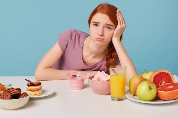 若い赤毛の少女は彼女の頭を手に持ってテーブルに座って悲しいことに新鮮な果物の重要性を理解しています