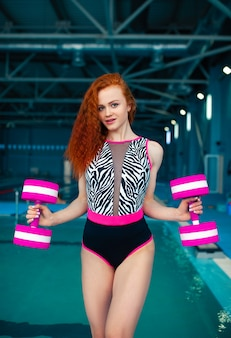 Young red-haired girl stands with the dumbbells  swimming pool
