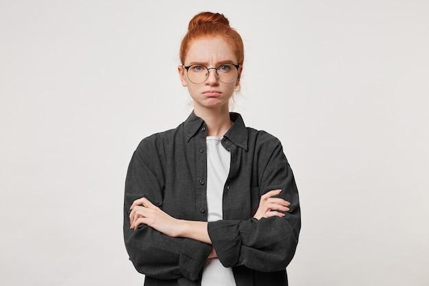 Una giovane ragazza dai capelli rossi con i capelli raccolti negli occhiali sta con le braccia conserte