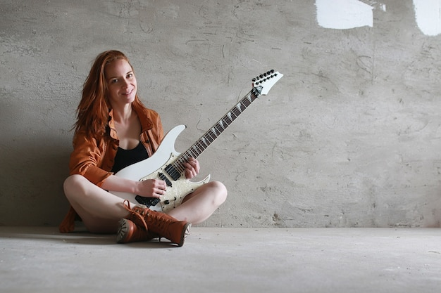 전기 기타와 함께 젊은 나가서는 소녀. 가죽 자 켓에 록 음악가 소녀입니다. 그녀는 아름다운 가수이자 록 음악을 연주하는 연주자입니다.
