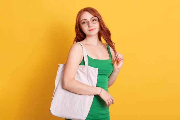 Young red haired girl with white blank cotton shopper tote bag wearing green t-shirt