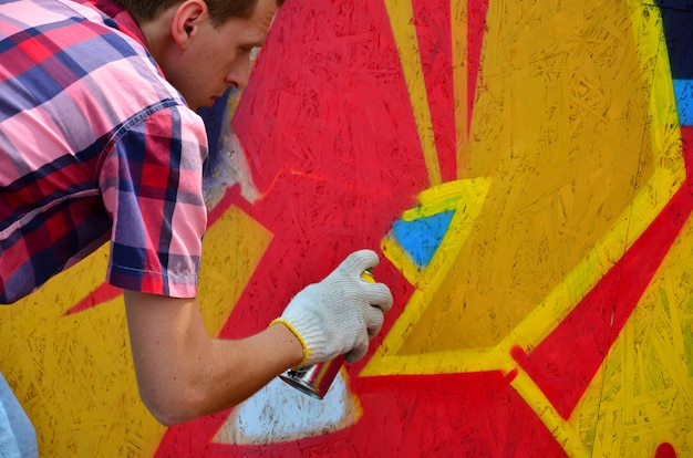 A young red-haired graffiti artist paints a new graffiti on the wall.