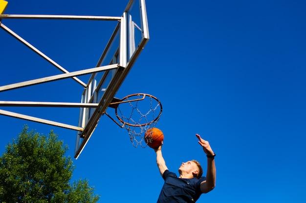 짙은 파란색 티셔츠를 입은 젊은 빨간 머리 남자가 야외에서 푸른 하늘을 배경으로 농구 골대에 공을 던졌습니다